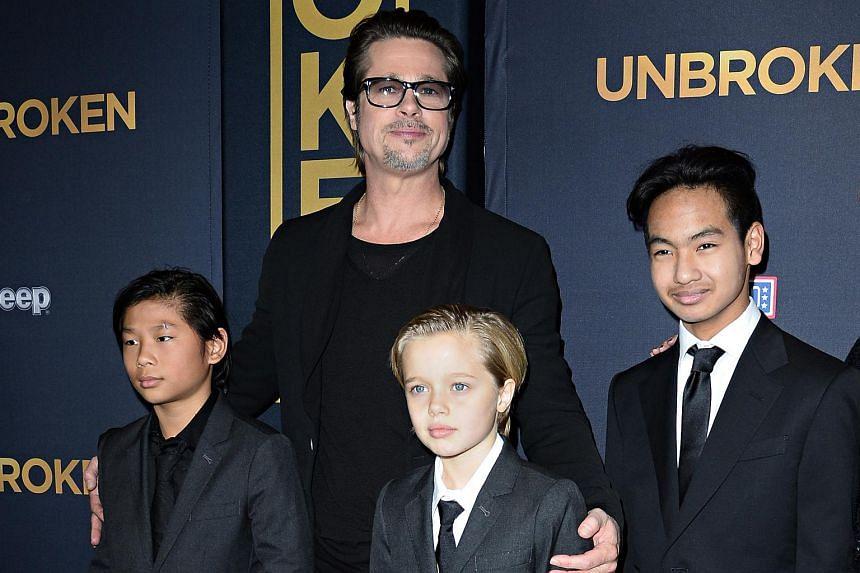 Brad Pitt and children Pax Jolie-Pitt (left), Shiloh Jolie-Pitt (centre) and Maddox Jolie-Pitt as they arrive for the US premiere of Unbroken on Dec 15, 2014.