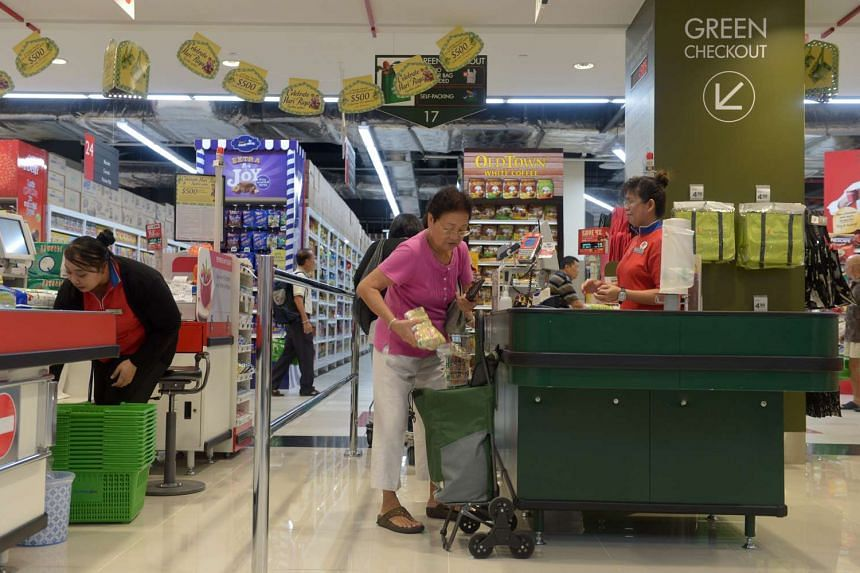 A customer (right) at the green checkout, a counter that does not provide customers with plastic bags for their purchases, to encourage customers to bring their own shopping bags.