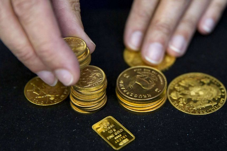 A worker places gold coins on display at Hatton Garden Metals precious metal dealers in London.