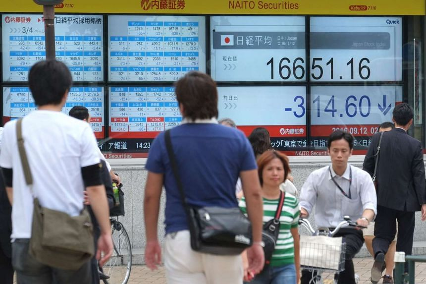 Pedestrians walking past an electric quotation board displaying the Nikkei key index of the Tokyo Stock Exchange in Tokyo on Sept 12, 2016.