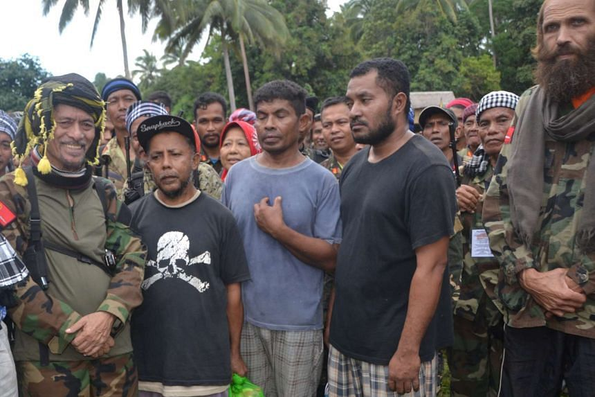 Three Indonesian nationals and Norwegian national Kjartan Sekkingstad (right) standing next to Moro National Liberation Front (MNLF) leader Nur Misuari and other members of the rebel group after the hostages are freed from the al Qaeda-linked Abu Say