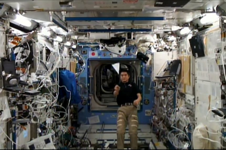 Japanese astronaut Takuya Onishi, 40, carrying out the Hillgrove Secondary 'Flying Paper Plane' experiment on board the Kibo module at the International Space Station on Sept 14.