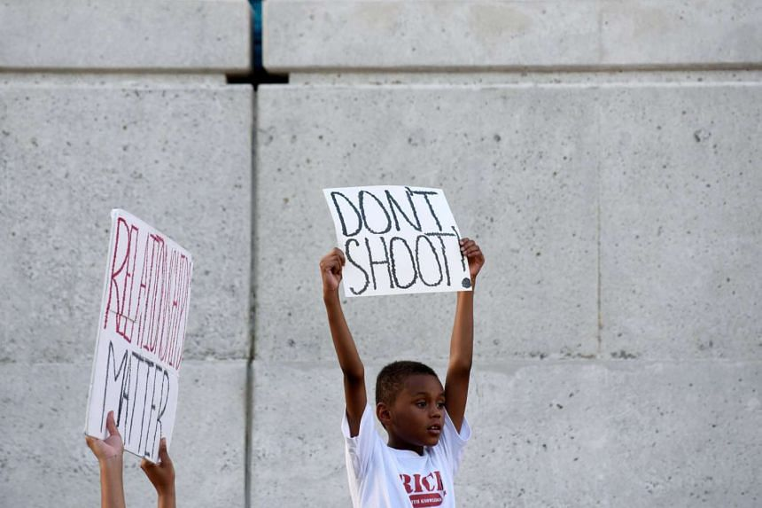 Eight year-old Angelo Estes Jr,  with other protesters outside the Tulsa Police headquarters on Sept 20, 2016, calls for the arrest of Officer Betty Shelby, who shot dead unarmed motorist Terence Crutcher.