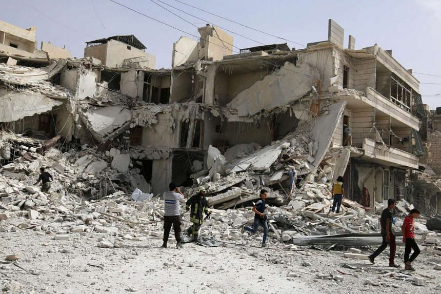 People inspect a damaged site after airstrikes on the rebel held al-Qaterji neighbourhood of Aleppo.