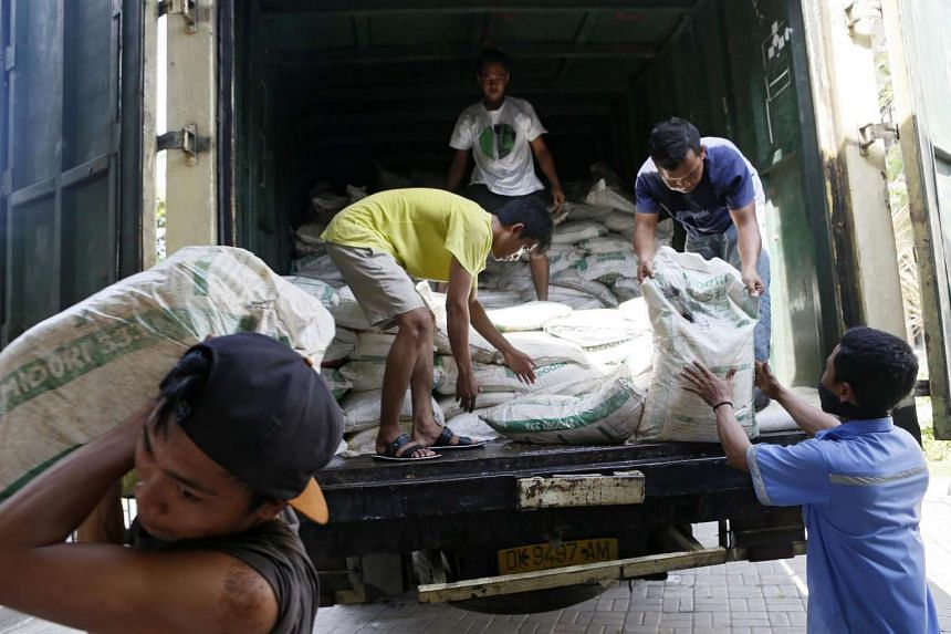 Indonesian workers unload sacks of ammonium nitrate illegally imported from Malaysia at a customs office in Denpasar, Bali, on Sept 22, 2016.