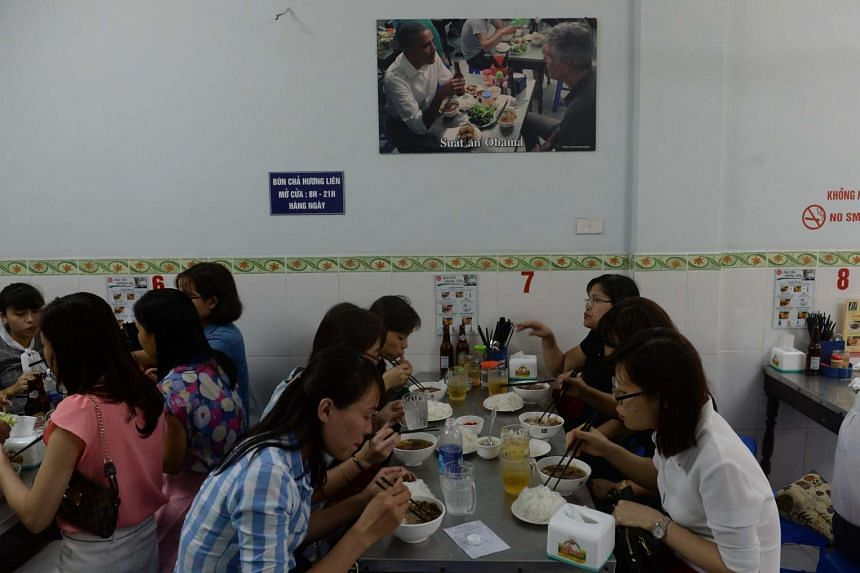 Customers eating under a picture showing US President Barack Obama eating during his visit to the same room of the Bun Cha Huong Lien restaurant in Hanoi.