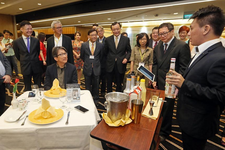 Minister for Manpower Lim Swee Say (seated) being served by Soh Shang Neng, 25, a graduating Shatec student, at Hotel Day 2016.