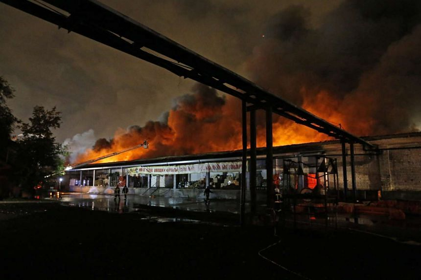 Russian fire fighters attempt to extinguish a fire at a workshop that produces plastic dinnerware in Moscow, Russia on Sept 22, 2016.