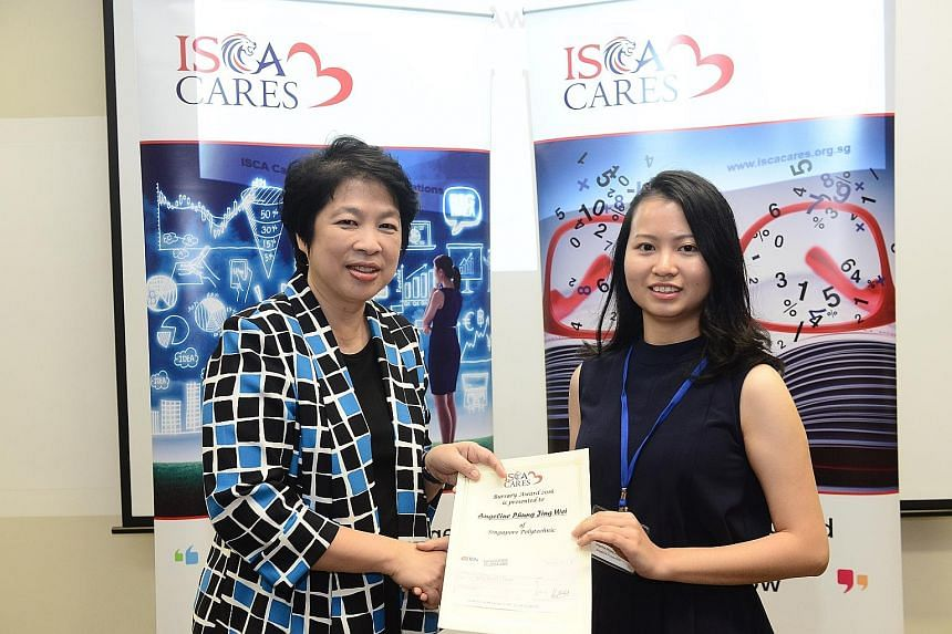 Ms Phung (right), a Singapore Polytechnic accountancy student, receiving her bursary from Mrs Lim, chairman of Isca Cares, on Tuesday.