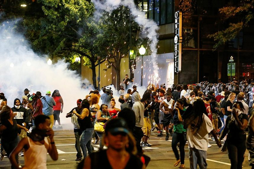 People dispersing as riot police launched flash-bang grenades in uptown Charlotte, North Carolina, during a protest on Wednesday against the fatal police shooting of a black man.