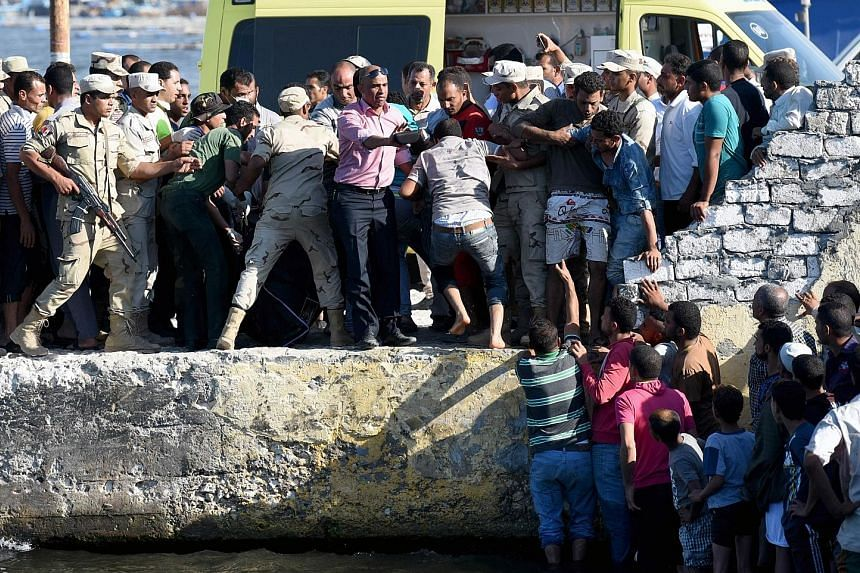 A crowd gathered as the bodies of drowned migrants were brought to shore in the Egyptian city of Rosetta on Wednesday.