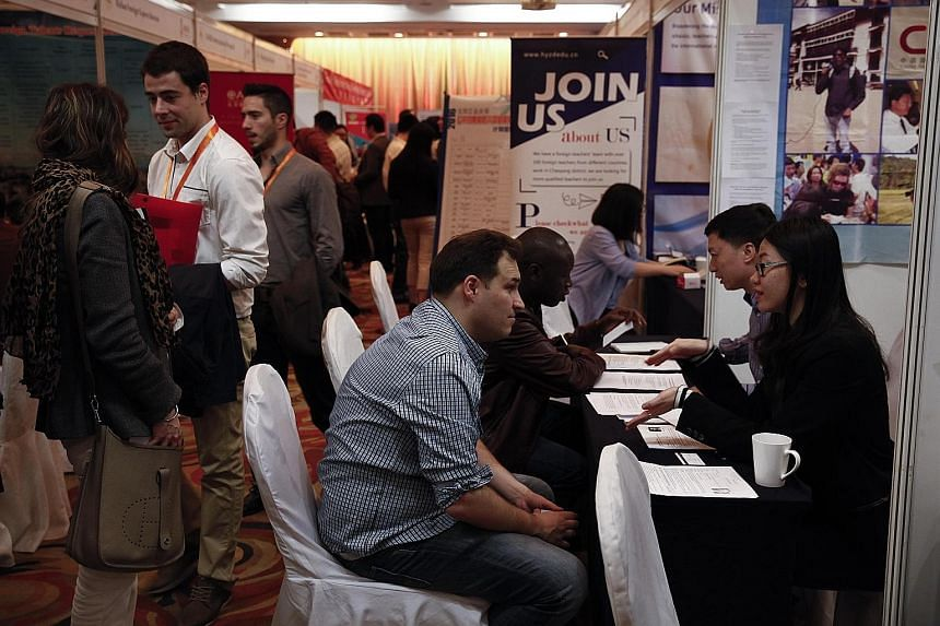 Job seekers talking to company representatives during a job fair for foreigners at a hotel in Beijing in April. The new work permit system is scheduled to be implemented nationwide on April 1 after being tested in nine cities and provinces, including