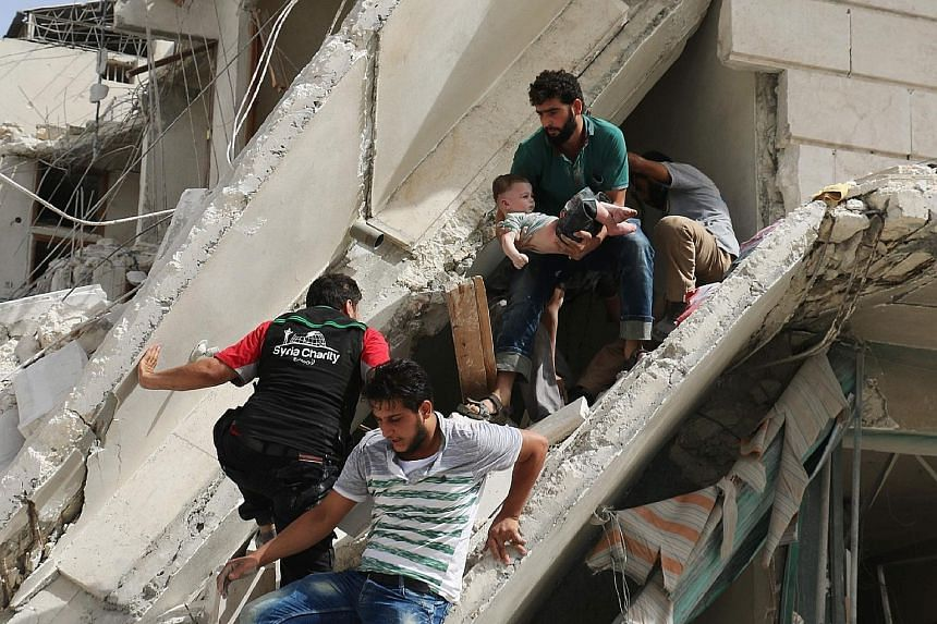 """A child being rescued from the rubble of a building in the Qatarji neighbourhood of Aleppo that was damaged in an air strike on Wednesday. US Secretary of State John Kerry has called for an immediate grounding of all military aircraft in """"key areas"""""""