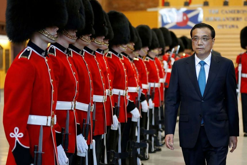 Chinese Premier Li Keqiang inspects the honour guard during a welcoming ceremony in Ottawa, Canada, Sept 22, 2016.