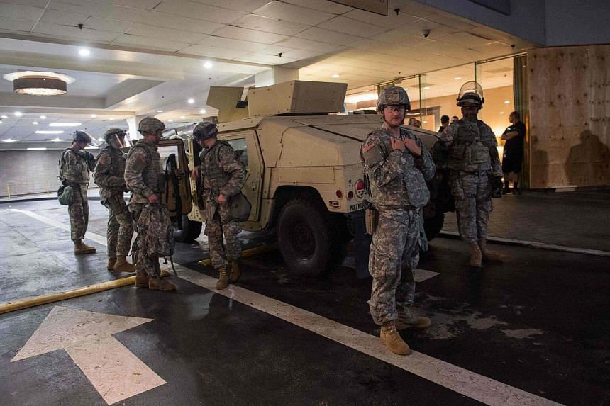 Members of the National Guard standing outside the entrance of a hotel in Charlotte, North Carolina, on Sept 22, 2016, after a state of emergency was declared following the shooting of Keith Lamont Scott.