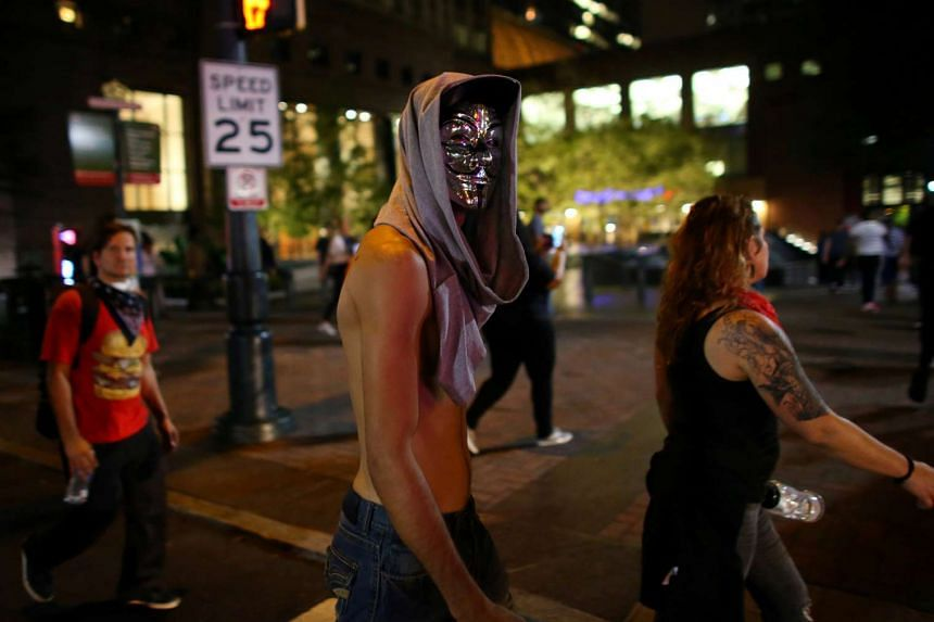 A masked demonstrator takes part in a protest against the police shooting of Keith Scott in Charlotte, North Carolina, on Sept 23, 2016.