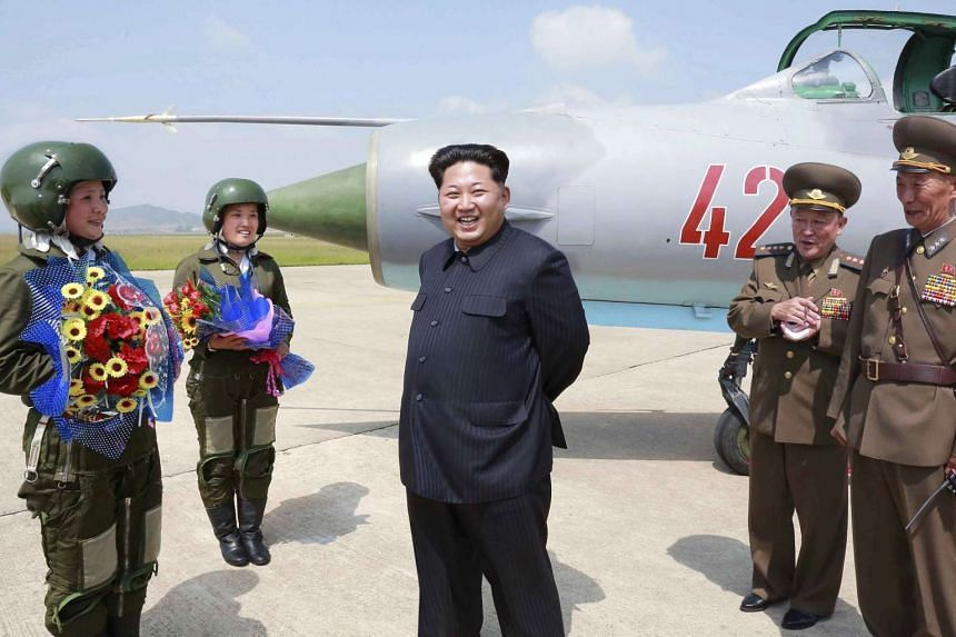 North Korean leader Kim Jong Un smiling as he attends a flight training session by female fighter pilots Jo Kum Hyang and Rim Sol in this undated photo released by North Korea's Korean Central News Agency on June 22, 2015.