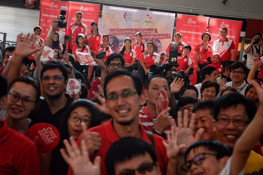 The crowd at Sengkang Sports Centre posing for a group photo with the Paralympians on stage.