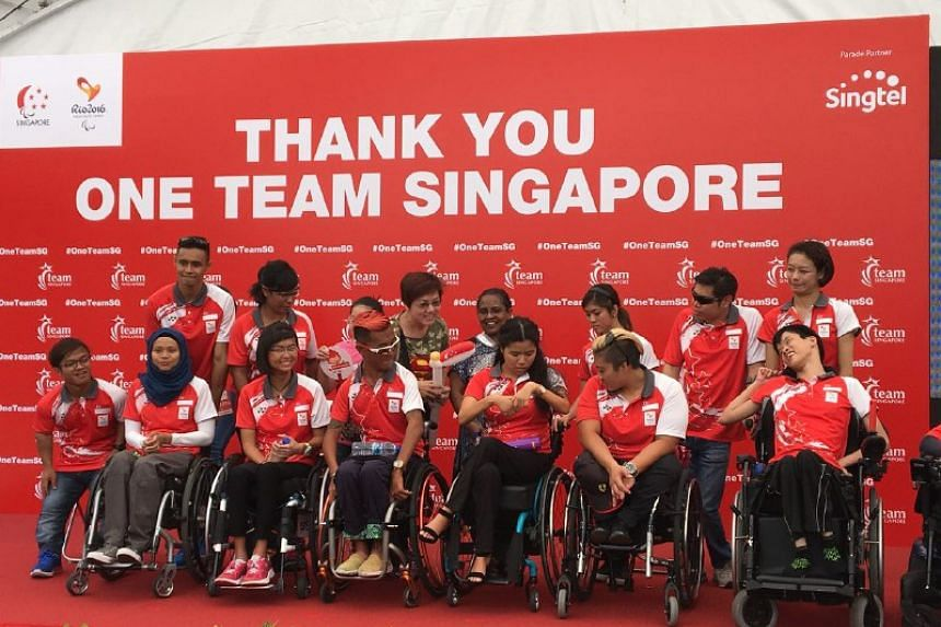 Paralympians taking a photo with supporters at VivoCity.