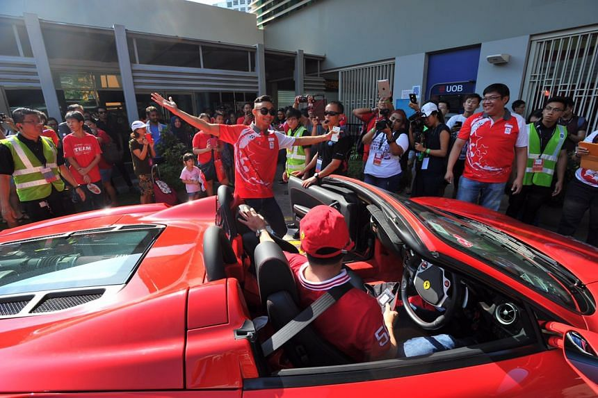 Para-athlete Suhairi bin Suhani posing for a photograph with a Ferrari.