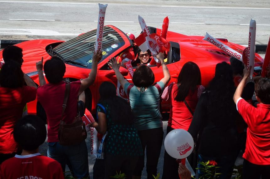 Paralympian Yip Pin Xiu waving to the crowd outside Braddell Heights CC.