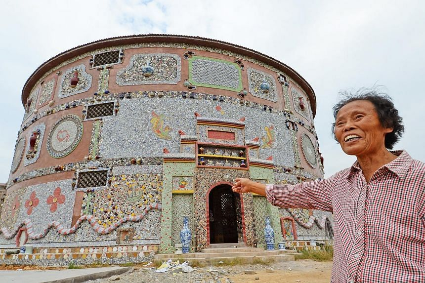 """Ms Yu Ermei, 86, showing the way to her """"porcelain palace"""", built at a cost of 6 million yuan (S$1.2 million). She started on the project five years ago. More than 60,000 pieces of porcelain ware were used to construct the building. Ms Yu runs a porc"""