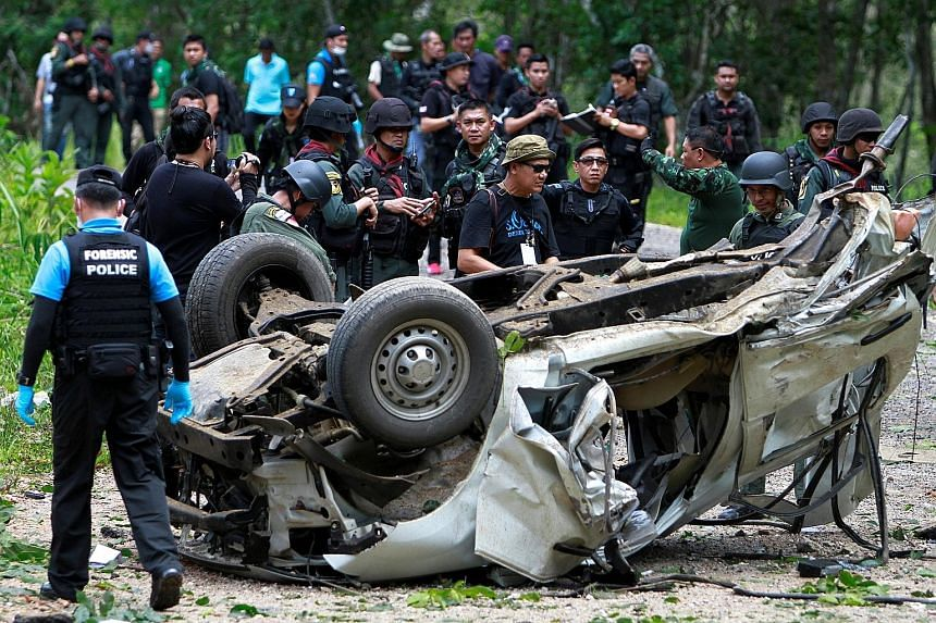 Members of the military inspecting the site of the roadside bomb attack in Krong Pinang district in the southern province of Yala, Thailand, yesterday.