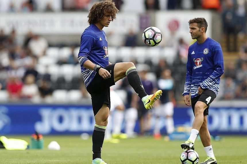 Chelsea's David Luiz (far left) will likely retain his place in central defence against Arsenal today, while team-mate Cesc Fabregas will be hoping that he is in the starting line-up after scoring a brace against Leicester City in the League Cup on T