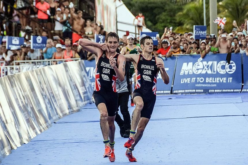 """British athlete Alistair Brownlee (left) helping his younger brother Jonathan across the line during the World Triathlon Championships in Mexico on Sept 18. """"It was a natural human reaction,"""" the older sibling said after the race."""