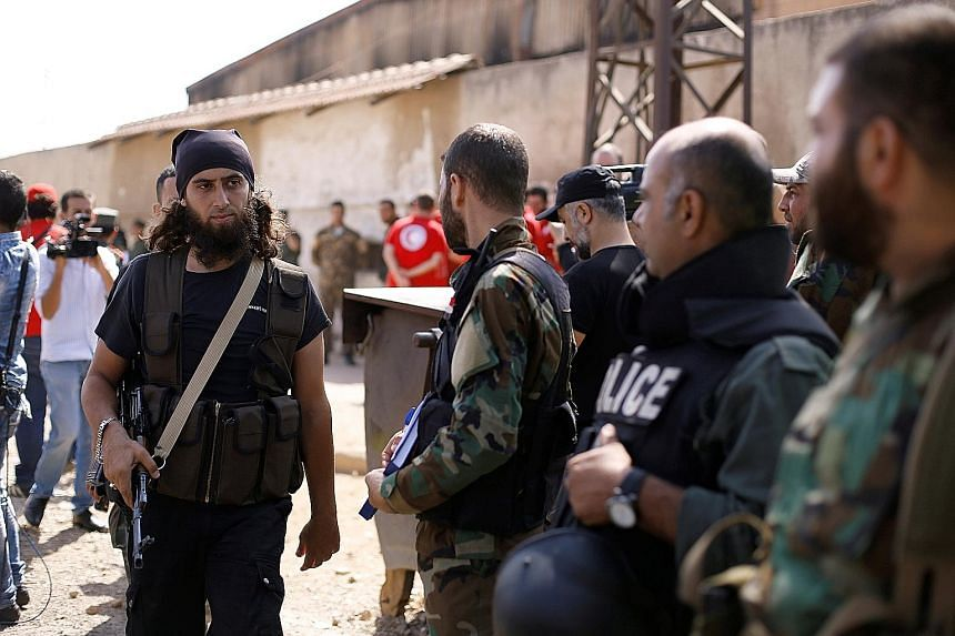 A rebel fighter (left) next to Syrian army soldiers, prior to evacuating the besieged Waer district in the central Syrian city of Homs, after a local agreement was reached between rebels and Syria's army on Thursday.