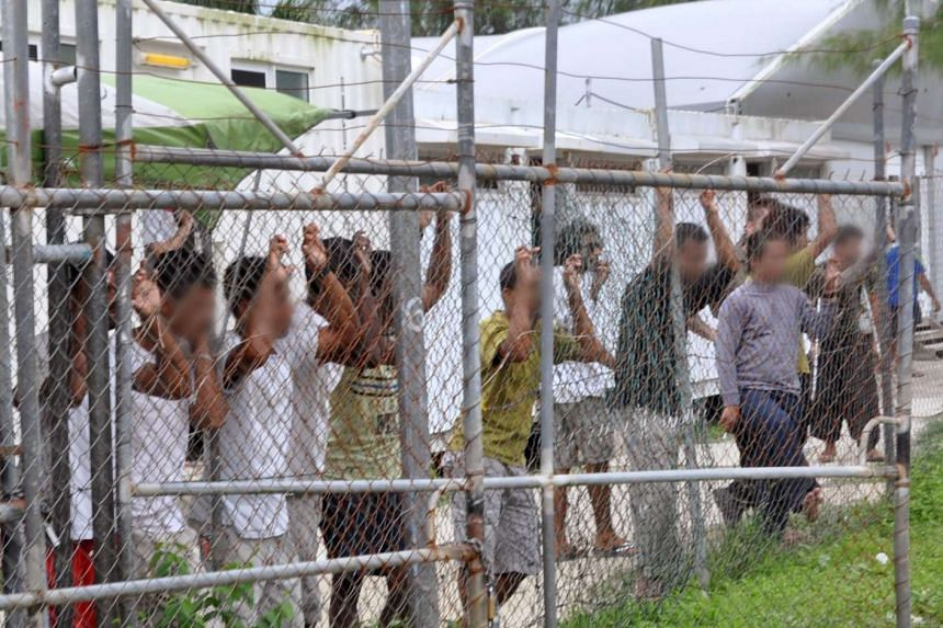Asylum seekers looking at the media from behind a fence at the Manus Island detention centre, Papua New Guinea in this picture taken on March 21, 2014.