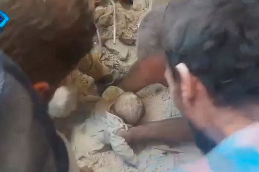 A still image from video posted on social media web sites Sept 23, 2016, shows a baby being rescued from rubble of a collapsed building in Aleppo.