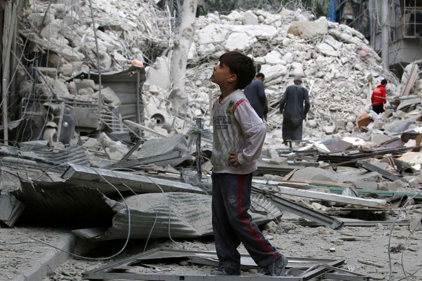 A boy inspects a damaged site after airstrikes on the rebel held Tariq al-Bab neighbourhood of Aleppo on Sept 23, 2016.