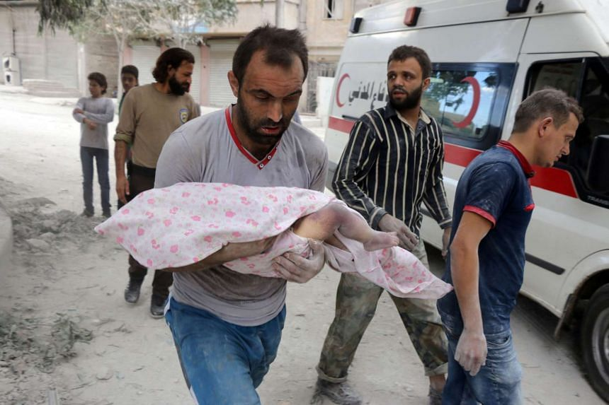 A Syrian man carries the body of an infant retrieved from under the rubble of a building following a reported airstrike on Sept 23, 2016, on Aleppo.