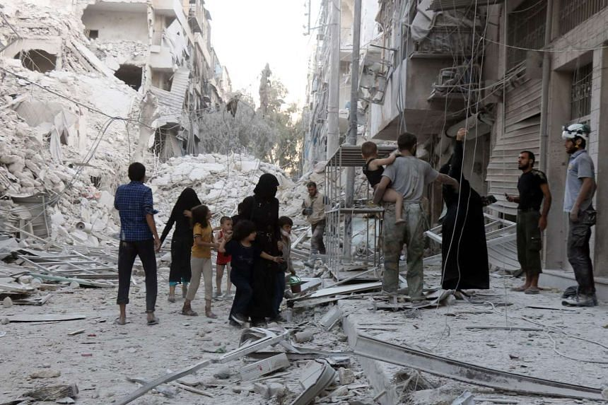 A Syrian family leaves the area following a reported airstrike on Sept 23, 2016, on the al-Muasalat area of Aleppo.
