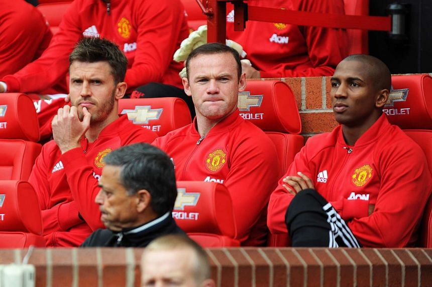 Manchester United's Wayne Rooney (centre) is flanked by Michael Carrick (left) and Ashley Young (right) on the bench.