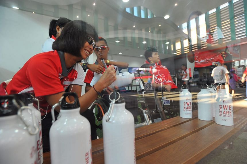 Sailor Yap Qian Yin signing bottles to be given out during a quiz later.