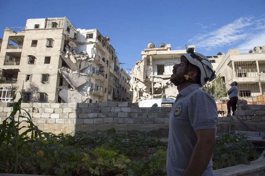 A Syrian rescuer looks towards the sky following an air strike in the rebel-held Ansari district in Aleppo on Sept 23, 2016.