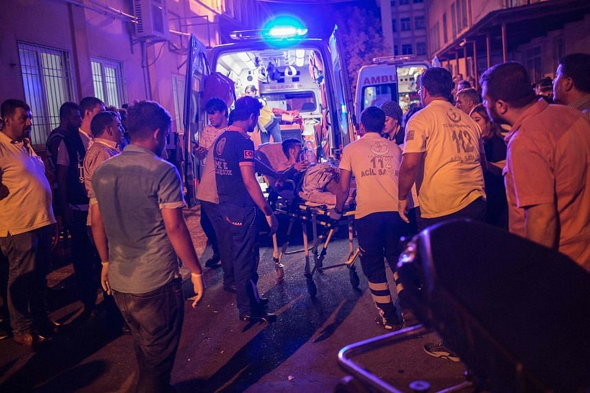 First aid officers carrying an injured man into an ambulance following a suicide bomb attack at a wedding party in Gaziantep, on Aug 20, 2016.