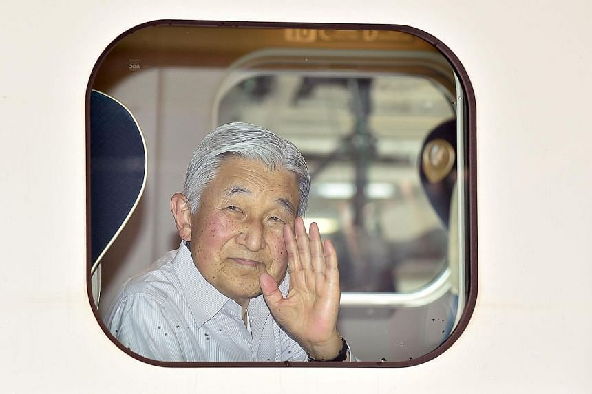 Emperor Akihito waves from a bullet train before departing Tokyo on Aug 20 for a visit to Nagano and Gunma prefectures. The Emperor has hinted that he wishes to step down.