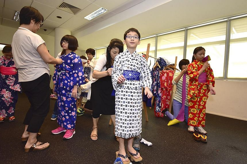 Children trying on traditional Japanese clothing such as the yukata and kimono. Moshi Moshi, Hello! is an event that promotes intercultural exchange and mutual understanding between children from the local and Japanese communities.
