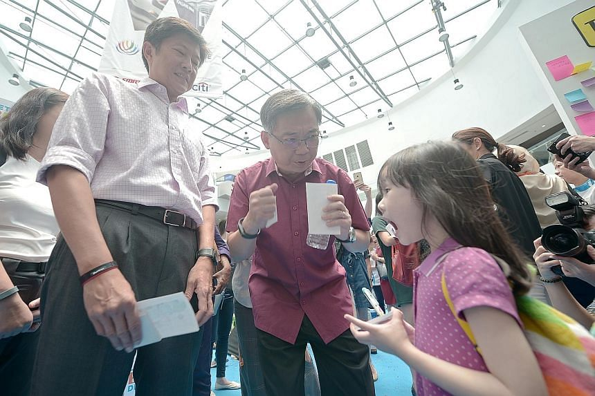 Mr Ng (at left) and Mr Gan having a conversation with five-year-old Kayleigh Lim about eating right. The two ministers are co-chairs of the the 16-member Diabetes Prevention and Care Taskforce.
