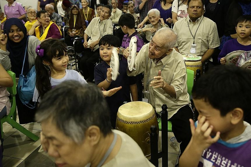 Mr Loh Soh Chye, 77, playing the drum and cymbals with six-year-olds Emily Yuliani Fichera (far left) and Ezra Gabriel Dela Cruz. Mr Loh was one of 38 residents from Apex Harmony Lodge who participated in an intergenerational exchange with 59 childre