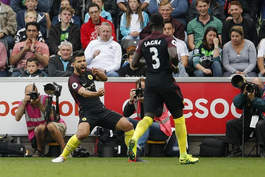 Manchester City's Sergio Aguero celebrating with Bacary Sagna after the first of his two goals against Swansea yesterday. He returned to domestic duties after a three-match suspension and took just nine minutes to open the scoring in the 3-1 win over