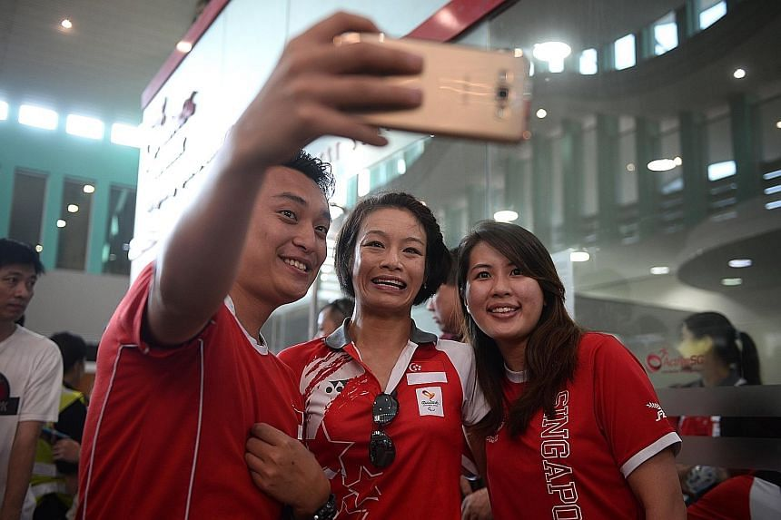 Paralympic archer Nur Syahidah Alim (left) and track and field participant Muhammad Diroy Noordin (centre) arriving at VivoCity, where about 400 fans had been waiting to congratulate the sportsmen. Swimmer Yip Pin Xiu, who won two golds, greeting the