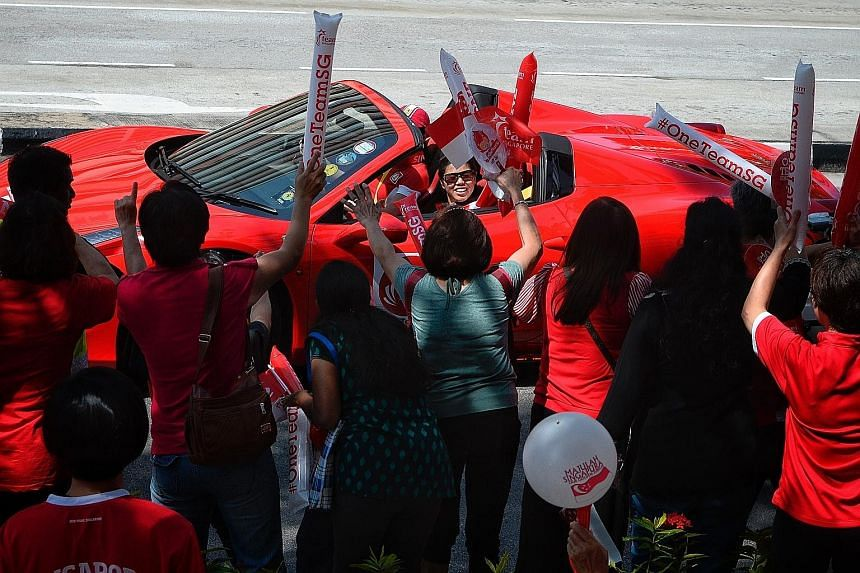 Rio Paralympics double swimming gold medallist Yip Pin Xiu waving to supporters outside Braddell Heights Community Club during the Singapore Paralympians' celebratory parade yesterday morning. The 13 Paralympians braved the hot sun as they travelled