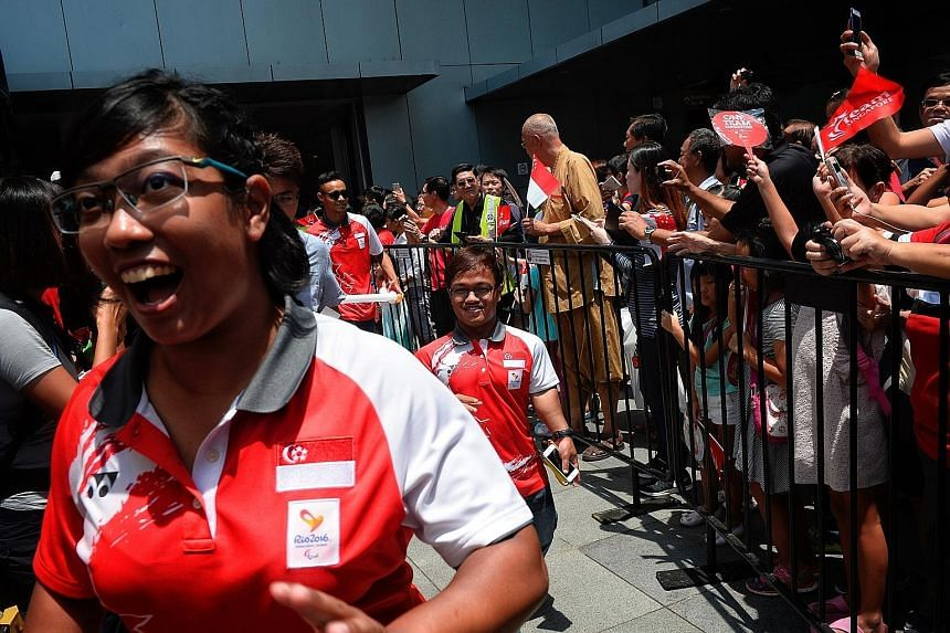 Supporters taking a wefie with equestrian para-athlete Laurentia Tan (centre) at the Sengkang Sports Centre during the Paralympians' first stop on the One Team Singapore celebratory parade.
