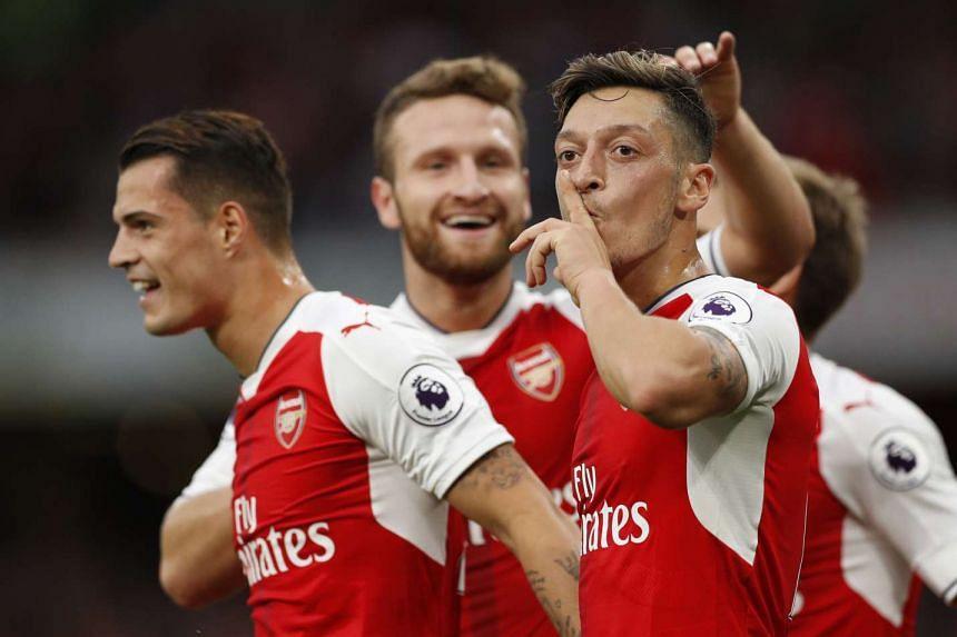 Arsenal's Mesut Ozil celebrates scoring their third goal with team mates.