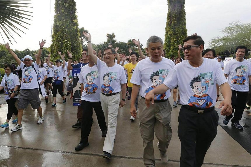 Health Minister Gan Kim Yong (middle, waving) flagged off the National Taxi Association's 3km walkathon for diabetes awareness.