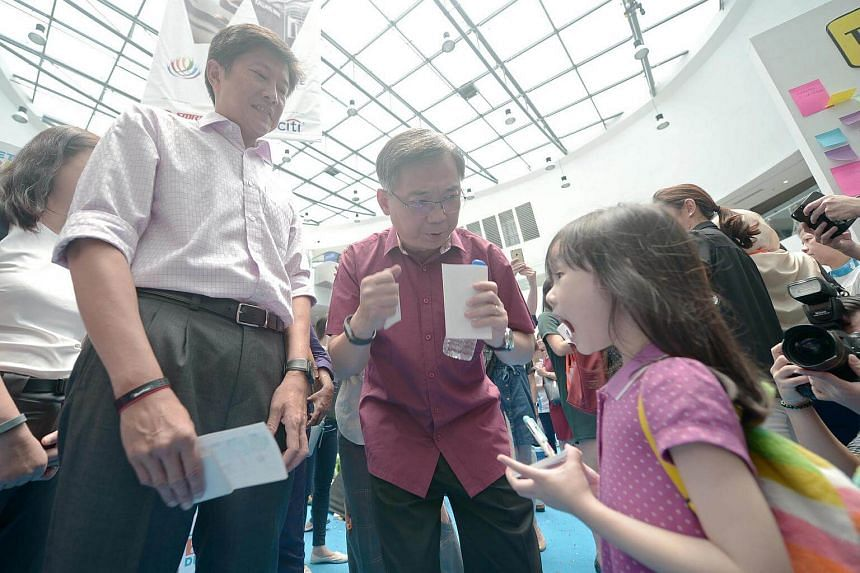 Acting Minister for Education Ng Chee Meng (left) and Health Minister Gan Kim Yong (right) speaking with 5-year-old Kayleigh Lim about eating right.